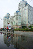 People ride bicycle with high-rise building background. HO CHI MINH, VIET NAM- DEC 15: People ride bicycle on street with high-class high-rise building Stock Image