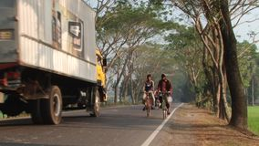 People ride bicycles by the road in Jessore, Bangladesh. JESSORE, BANGLADESH – FEBRUARY 19, 2014: Unidentified people ride bicycles by the road on stock video footage