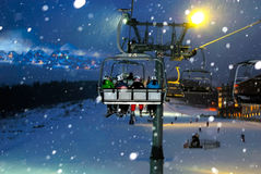 People ride in the chairlift at night. People ride in the chair lift, elevator, night landscape Stock Photo