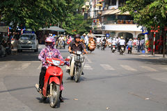 People ride motorbikes on busy road in Hanoi Stock Images