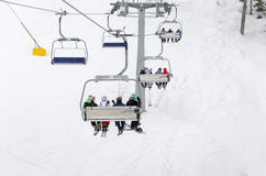 People ride the ski chair lift up the mountain Stock Photography