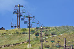 People ride ski lift in the summer. Ski lift used to take people up a hill in the summer Royalty Free Stock Photography