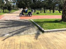 People ride in a small electric car, a golf car on the seafront on a sandy beach. Georgia, Batumi, April 17, 2019 royalty free stock image
