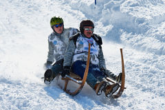 People ride traditional horn-sledge at 12-th annual Horn-Sledge Race from Alpiglen to Grund in Grindelwald, Switzerland. stock images