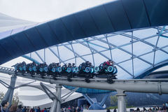 People ride TRON Lightcycle in Shanghai. Shanghai, China. April 20, 2017: Group of people riding TRON Lightcycle Power Run in Shanghai Disneyland, China Stock Photo