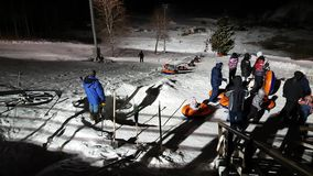People ride on tubing. JAN 06, 2017 YAHROMA, RUSSIA: People having fun with tubing ride in Yahroma park near by Moscow at night stock footage