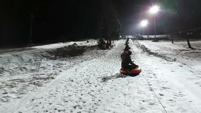 People ride on tubing. JAN 06, 2017 YAHROMA, RUSSIA: People having fun with tubing ride in Yahroma park near by Moscow at night stock video