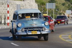 People ride in a vintage taxi car in Havana, Cuba. Stock Images