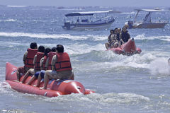 People riding on a banana boat in bali beach Stock Photos