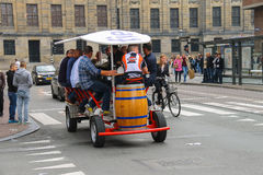 People riding beer bicycle in Amsterdam, the Netherlands. Amsterdam, the Netherlands -October 03, 2015: People riding beer bicycle in historical city centre Royalty Free Stock Photo
