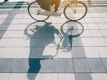 People Riding Bicycle shadow on street Urban Ecology lifestyle. Commuter travel royalty free stock photo