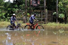 People riding bicycles on the flooded roads. Unidentified people riding bicycles on the flooded roads on August 21,2018 in Thiruvalla, Kerala, India. Kerala was stock image
