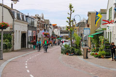 People riding bicycles on Haltestraat street in Zandvoort Royalty Free Stock Image