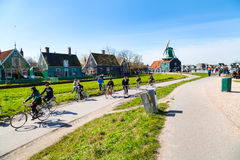 People riding bicycles, houses and windmill in Zaanse Schans, Holland Royalty Free Stock Photos