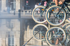 People riding bicycles in the mirror fountain. In front of Place de la Bourse in Bordeaux, France Royalty Free Stock Photos