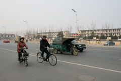 People riding bikes in China, and a motorised utility bike. Fuyang, China - February, 17 2011 - People riding bikes in China, and a motorised utility bike Stock Photos