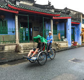 People riding cyclos on main road at Ancient town in Hoi an, Vietnam. Hoi An is a city on Vietnam's central coast known for its well-preserved Ancient Town Stock Photos