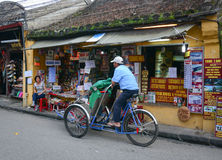 People riding cyclos on the main street in Hoi An, Vietnam Stock Photo