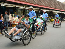 People riding cyclos on the main street in Hoi An, Vietnam Stock Photography
