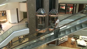People riding down escalator next to elevators within mall (1 of 2). A view or scene of Shopping stock video