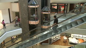 People riding down escalator next to elevators within mall (2 of 2). A view or scene of Shopping stock video footage
