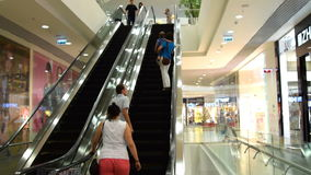 """People riding escalator in trade center. NOVOSIBIRSK, RUSSIA€"""" JULY 31, 2015: People riding up and down the escalator in modern shopping mall stock video footage"""