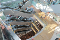 People riding on escalators in a busy peak mall in Hong Kong Stock Image