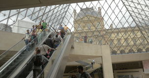 People riding escalators underground the Louvre Pyramid stock video footage