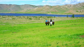 People riding horses in Mongolian landscape Stock Photo