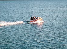 People riding a motorboat in a calm ocean. royalty free stock photography
