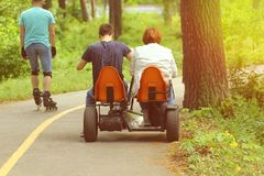 People riding pedal car, back view. New sports and recreation activities in the spring sunlit park. Royalty Free Stock Image