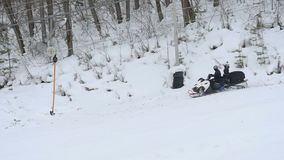 People are riding on snowmobile on downhill stock footage
