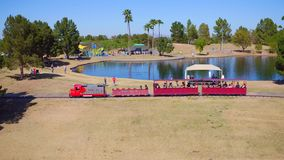 People Riding a Train Around a Lake at a Park stock video footage