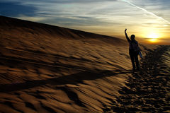 People rising arm in the desert in the evening Stock Image