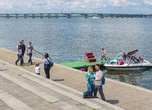 People on the river Dnepr embankment during Victory Day celebrations. DNEPROPETROVSK, UKRAINE - May 09, 2016:People walking on the river Dnepr embankment during stock photo