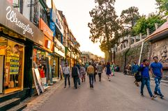 People roaming past branded showrooms on mall road Shimla. Shimla, India - 25th Apr 2018: People roaming in front of branded shops on the mall road in Shimla Royalty Free Stock Photos