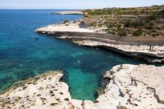People at the rocks at Marsaskala beach, Malta. Marsaskala, Malta - May 31: People sunbathing and swimming on the rocks of Marsaskala beach, Matla at May 31 Stock Images