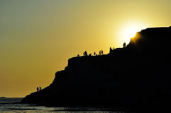 People on rocky cliff at sunset Royalty Free Stock Photography