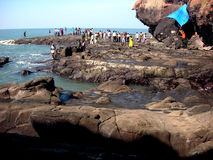 People on rocky shoreline. Scenic view of rocky coastline with group of people in background Royalty Free Stock Photography