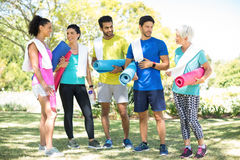 People with rolled exercise mats talking in the park. Group of people with rolled exercise mats talking in the park Stock Photos