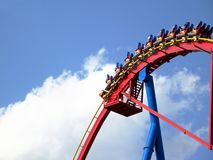 People in roller coaster againt bright blue sky Royalty Free Stock Photo