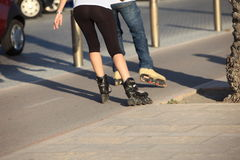 People rollerblading down a sidewalk Stock Photo