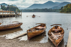 People row a boat on Derwent Water. KESWICK, UK - SEP 9, 2014: People row a boat on Derwent Water in the English Lake District Stock Photos