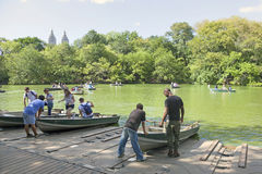 People row in boats on new york city central park pond near boat. New York City, 14 september 2015: people row in boats on new york city central park pond near Stock Images