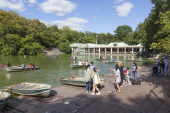 People row in boats on new york city central park pond near boat Royalty Free Stock Photo