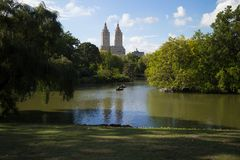 People in Rowboats on The Lake in Central Park, New York City. People in rowboats on The Lake in Central Park, Manhattan, NYC. The Majestic Apartments can be Stock Image