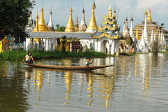 People rowing boat on Inle lake with pagoda background in Shan, Myanmar Stock Photography