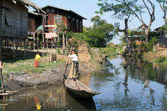 People on rowing a boat at the village of Maing Thauk Stock Images