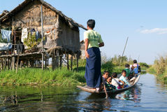 People on rowing a boat at the village of Maing Thauk Stock Photo