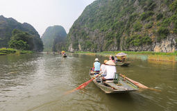 People rowing boats for carrying tourists in Tam Coc Royalty Free Stock Image